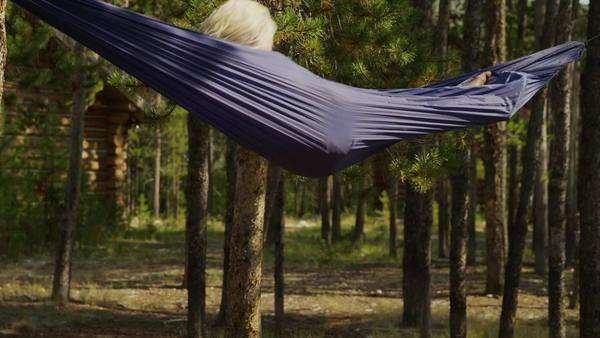 Medium shot of girl spinning and hanging in hammock in forest, Idaho Royalty-free stock video