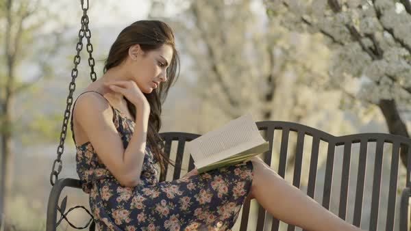 Medium slow motion shot of woman reading book on bench swing Royalty-free stock video