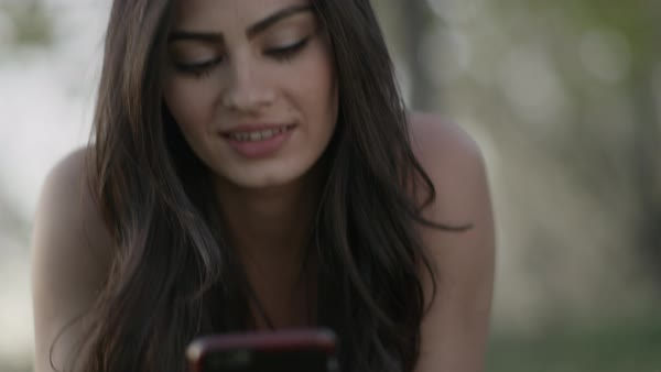 Close up shot of woman laying in grass texting on cell phone Royalty-free stock video
