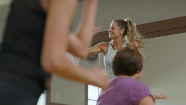 Medium panning shot of fitness instructor leading exercise class Royalty-free stock video