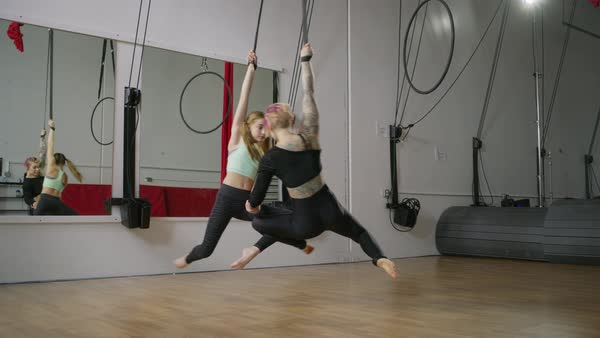 Medium slow motion panning shot of woman and girl practicing on aerial silks Rights-managed stock video