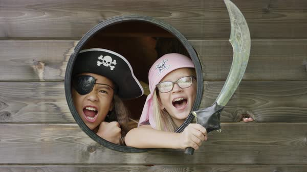 Close up of fierce girls playing pirate in window with sword / Provo, Utah, United States Royalty-free stock video
