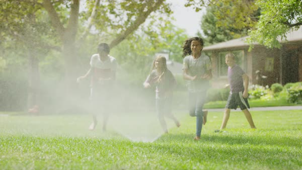 Children and dog running and jumping through sprinkler / Provo, Utah, United States Royalty-free stock video