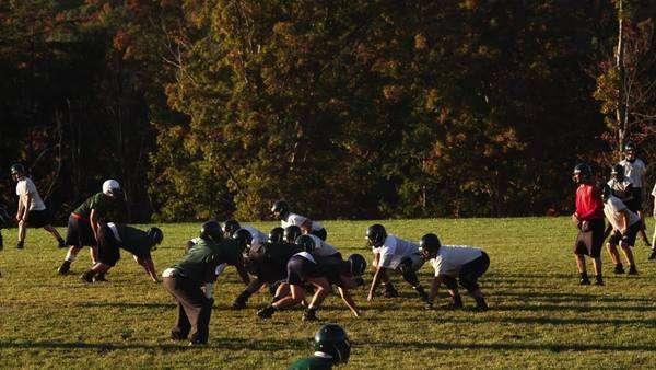 Slow Motion Medium Shot Pan Men Playing Football On Field Buena