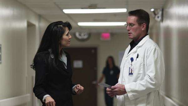 Medium shot close-up doctor and woman shaking hands in hospital corridor/ Payson, Utah, USA Rights-managed stock video