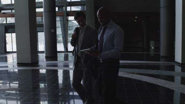 Medium shot dolly shot pan Business people looking at digital tablet while walking through office building's lobby, Las Vegas Royalty-free stock video
