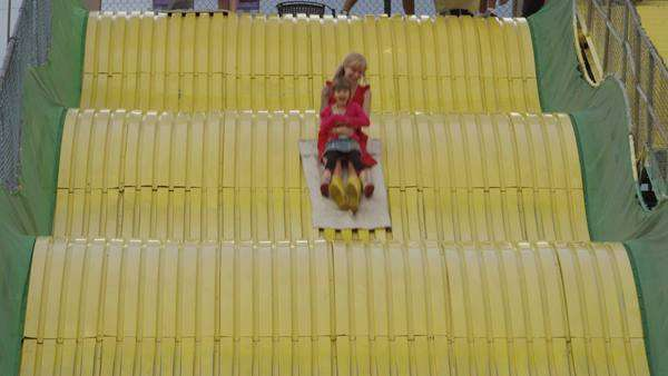 Medium shot of mother and daughter on large slide at amusement park / Salt Lake City, Utah, United States Royalty-free stock video