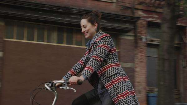 Low angle medium tracking shot of young woman riding bicycle on urban street / New York City, New York, United States Royalty-free stock video