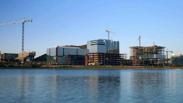 Office building construction project with lake in foreground, in Tempe, Arizona. The joint project is by Arizona State University and State Farm Insurance. Wide-view Timelapse. Royalty-free stock video