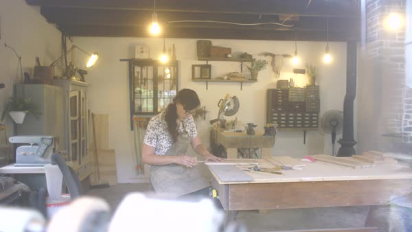 Medium wide shot of a woman polishing a wooden cutting board in a workshop Royalty-free stock video