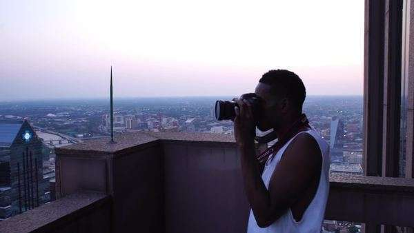Male photographer taking photo from skyscraper building at twilight Rights-managed stock video