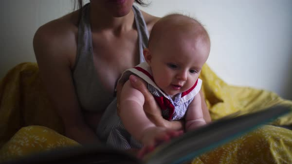 Hand-held close-up of mother reading to a baby from a book Royalty-free stock video