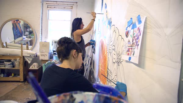 Hand-held shot of two women painting in a studio Royalty-free stock video