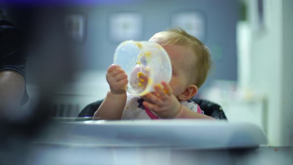 Hand-held shot of a baby licking a plastic container Royalty-free stock video