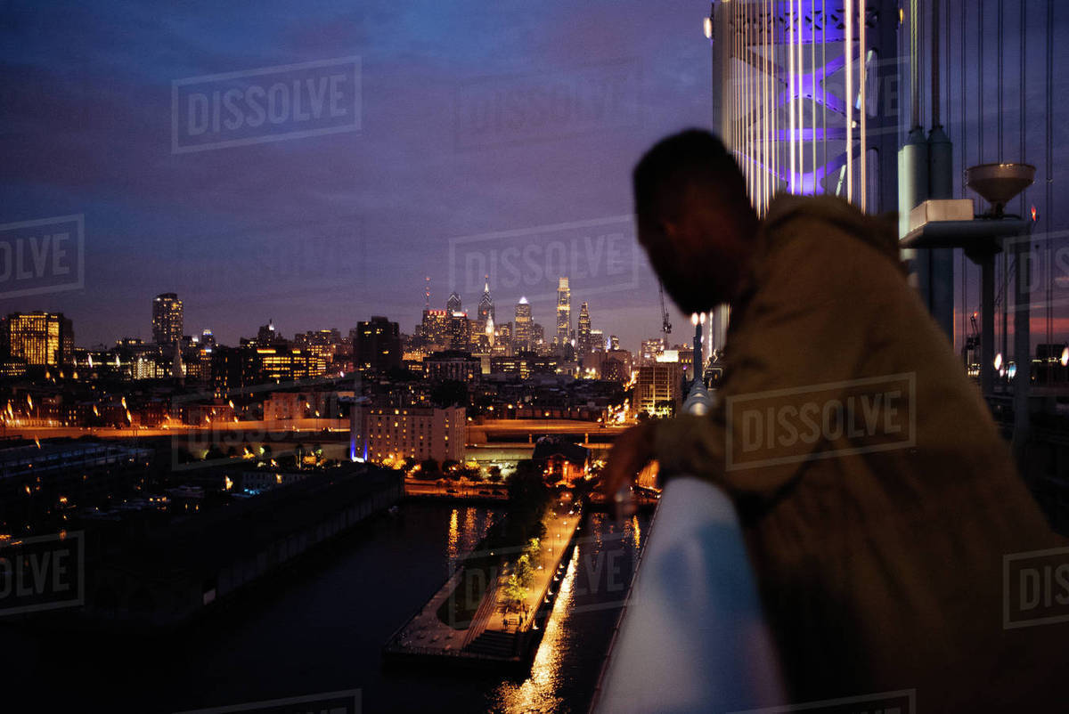Man looking at illuminated cityscape while standing on bridge at night Royalty-free stock photo