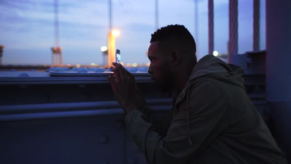 Medium shot of a man taking pictures on the Benjamin Franklin Bridge Royalty-free stock video