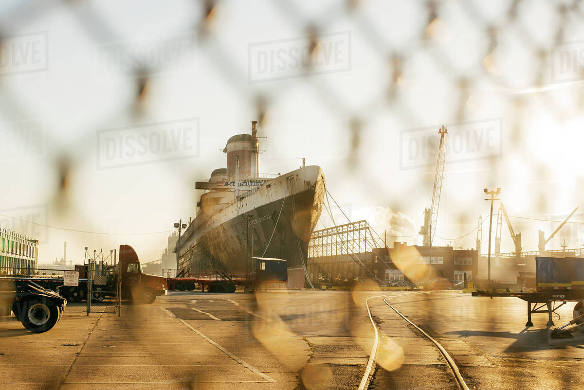 Military ship moored at harbor during sunset seen through wire mesh fence Royalty-free stock photo