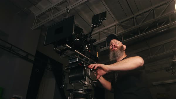 Bearded camera man panning pro rig with large lens in studio Royalty-free stock video