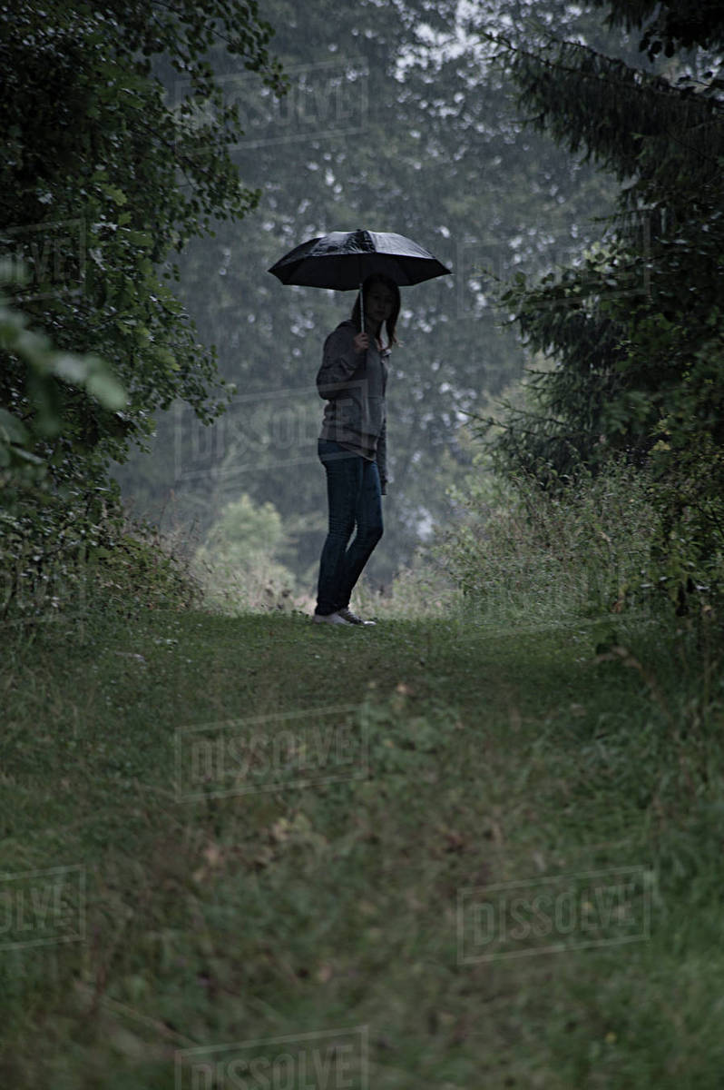 Young Woman With Umbrella In Rain Stock Photo Dissolve