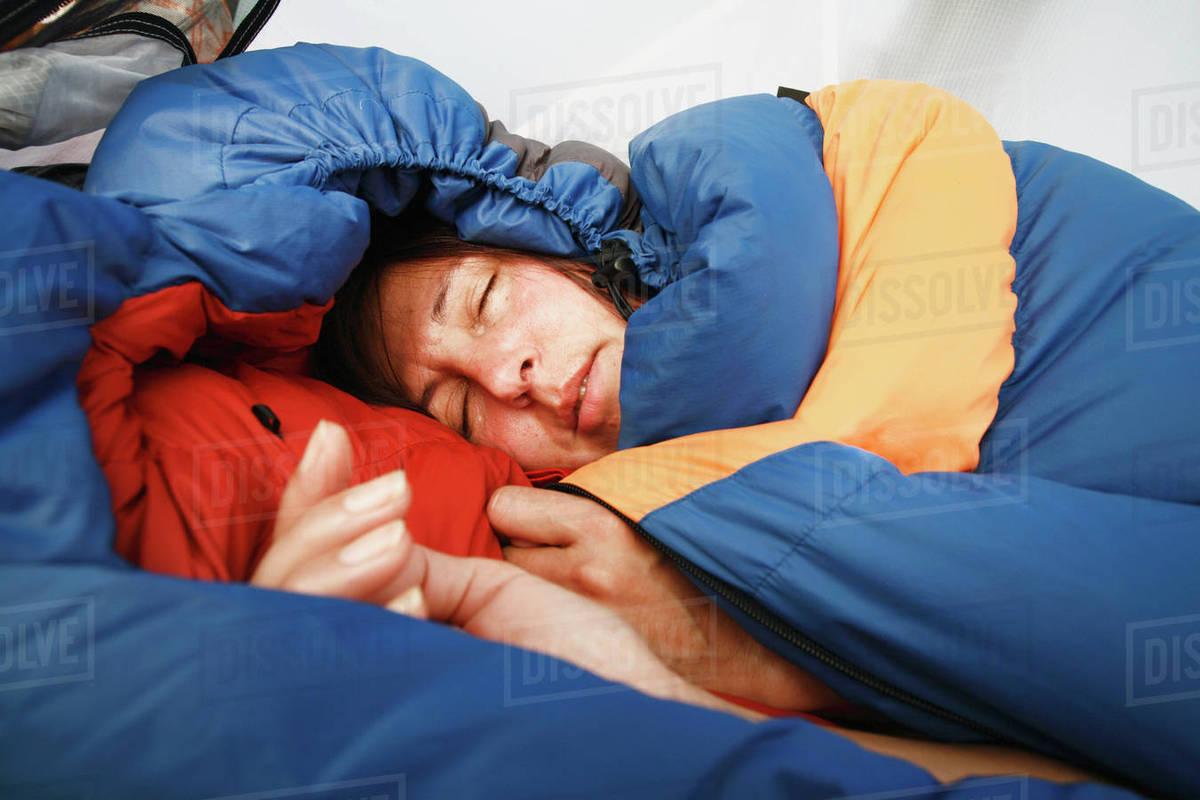 4d307d73c4 Woman sleeping in sleeping bag - Stock Photo - Dissolve