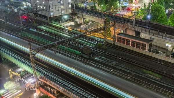 Timelapse of Tokyo trains and traffic at night. Six local and two bullet train (Shinkansen) tracks with car and foot traffic underneath. Royalty-free stock video