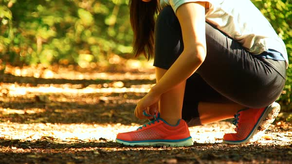 Female runner lacing her sneakers on a forest trail Royalty-free stock video