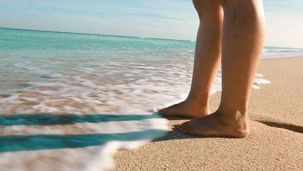 Ocean waves washing over womans feet Royalty-free stock video