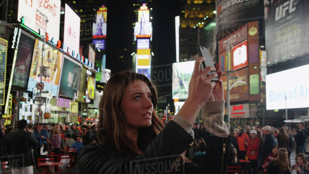 Tourist photographing iconic glowing billboard advertisements with cell phone in city intersection at night Royalty-free stock photo