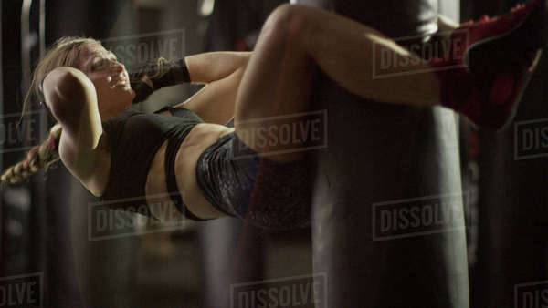 Selective focus view of female boxer working out and doing sit-ups on punching bag in gym Royalty-free stock photo