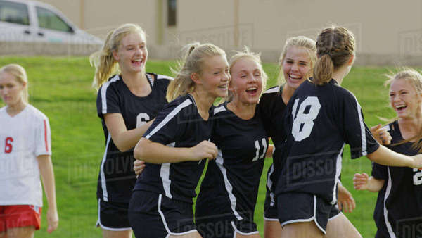 Proud athlete with soccer teammates cheering after game victory on field Royalty-free stock photo