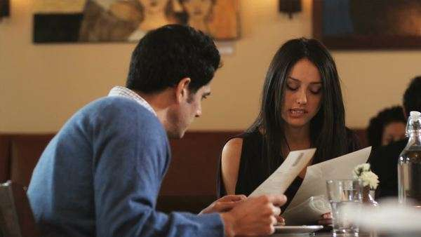 Couple looking at menus in a restaurant Royalty-free stock video