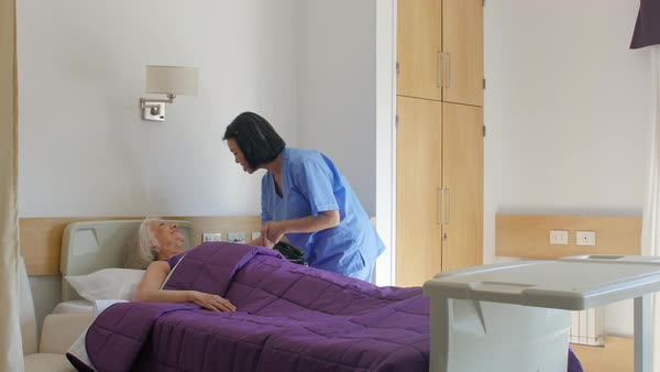 Asian nurse helping elder woman raising from hospital bed Royalty-free stock video