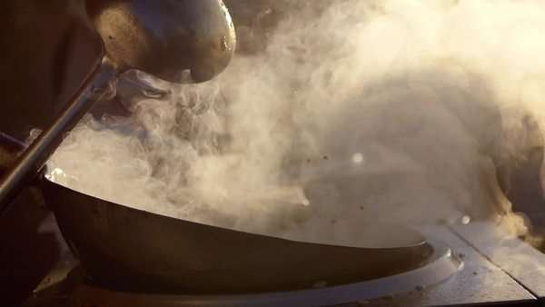 Slow motion: cook makes asian noodles in wok. a versatile round-bottomed cooking vessel, originating from china. asian food cooking. Royalty-free stock video