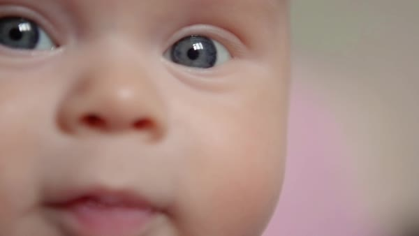 Close-up of baby's face looking around and in the camera. Royalty-free stock video
