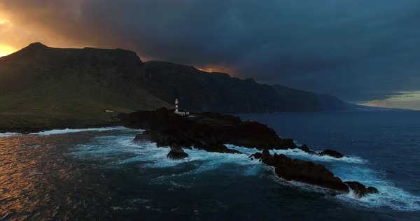 Aerial of lighthouse against big mountains and the sunset. Royalty-free stock video