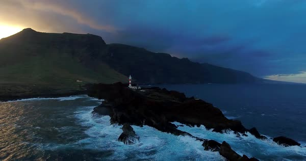 Aerial of lighthouse against big mountains at the sunset. Royalty-free stock video