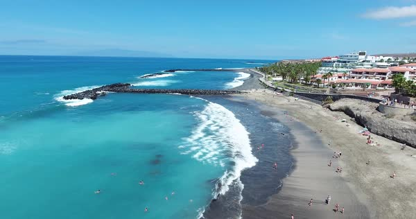 Canary Islands beach aerial shot with waves on the beach and swimming people. Royalty-free stock video