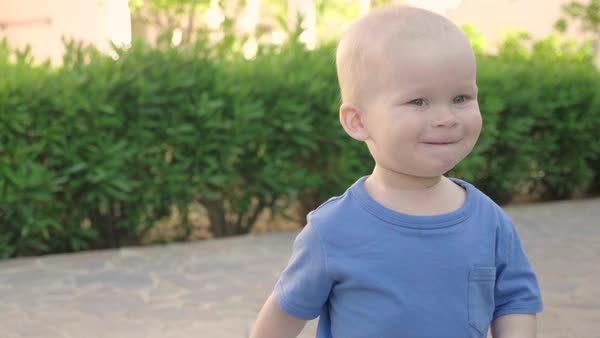 Portrait of a cute smiling blond boy enjoying a walk in a beautiful summer park, slow motion. Royalty-free stock video