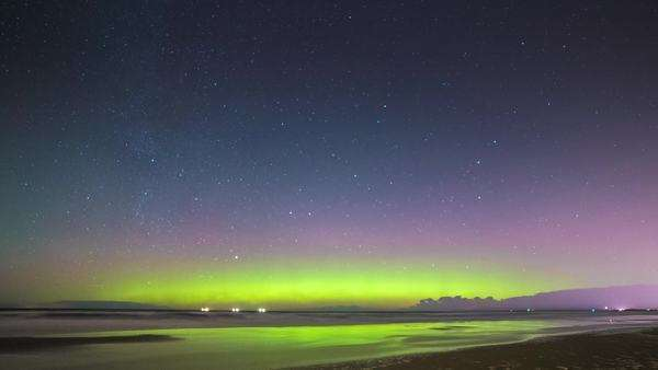 Timelapse of Northern lights on horizon as seen from a sandy beach in Riga, Latvia. Busy air traffic crossing the frame. Royalty-free stock video