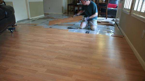 A workman or homeowner handyman type engaged in a DIY project of removing old laminate flooring to prepare for new floor covering. Royalty-free stock video