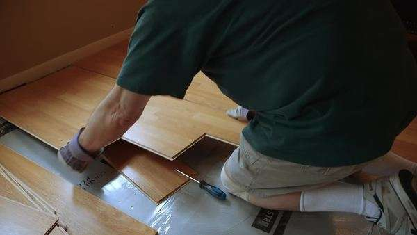 A workman or homeowner handyman type removing old laminate flooring in preparation of new floor covering as part of his DIY project. Royalty-free stock video