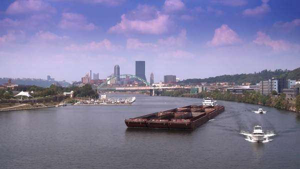 PITTSBURGH, PA - Circa September, 2015 - A tugboat pushes empty barge containers up the Monongahela River near Pittsburgh. Royalty-free stock video