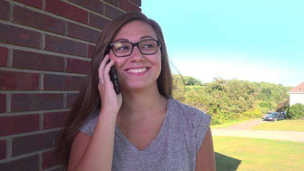 A teenager talks on her mobile phone outside of her home. Royalty-free stock video