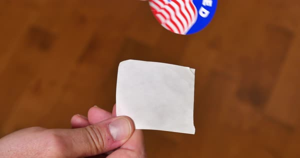 A man peels off an I Voted sticker.  	 Royalty-free stock video