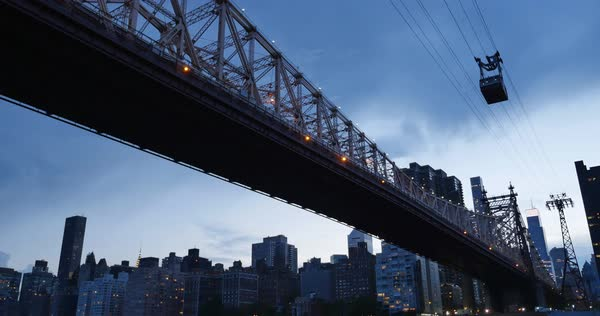 A nighttime establishing shot of the Ed Koch Queensboro Bridge between Manhattan and Brooklyn as the Roosevelt Island Tram carries passengers over the East River.  	 Royalty-free stock video