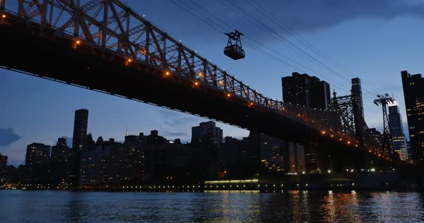 An evening establishing shot of the Ed Koch Queensboro Bridge between Manhattan and Brooklyn as the Roosevelt Island Tram carries passengers over the East River.	 	 Royalty-free stock video