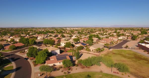A flyover aerial establishing shot of a typical Arizona residential neighborhood. The Superstition Mountain range in the distance. Phoenix suburb.	 	 Royalty-free stock video