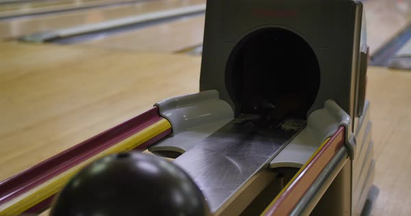 Slow tracking shot of people getting their balls from the ball return of a bowling alley. Extreme shallow DOF.    Royalty-free stock video