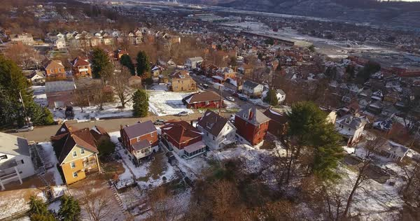 A slowly moving reverse aerial winter view of a typical Western Pennsylvania residential neighborhood and valley community. Royalty-free stock video