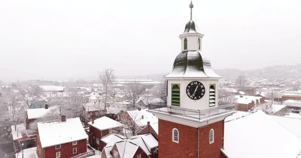 AMBRIDGE, PA - Circa March, 2017 - A slowly moving forward snowy establishing shot of St. John's Lutheran Church in Old Economy Village.  Royalty-free stock video